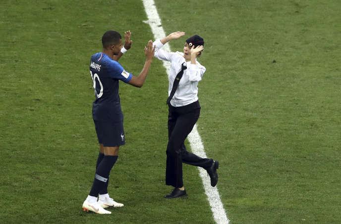Kylian Mbappé et une membre des Pussy Riot ayant fait une intrusion sur le stade, en pleine finale de la Coupe du monde, le 15 juillet à Moscou.