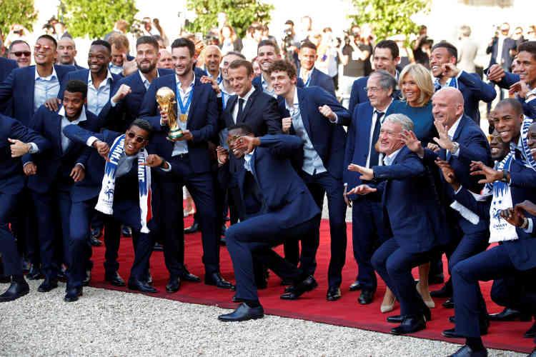 Arrivés pour une réception en leur honneur, l'équipe de France pose dans la cour de l'Elysée avec Brigitte et Emmanuel Macron.