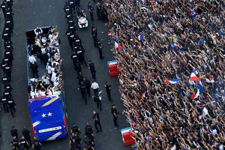 Ils viennent de tourner sur les Champs-Elysées, il est environ 19 h 20et c'est un bruit assourdissant qui les accueille. Rassemblée depuis plusieurs heures, une foule en délire aux couleurs bleu, blanc, rouge a accueilli ses 23 héros, arrivés un peu plus tôt de Russie. Il y a plus de cinq mètres entre la foule et les joueurs.