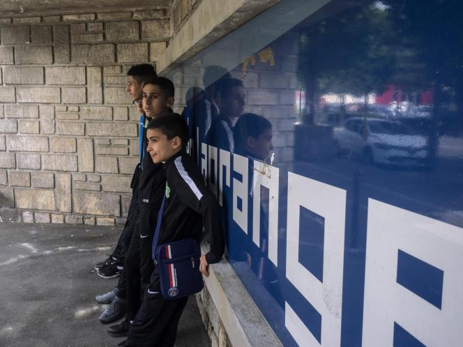 Devant le stade Léo-Lagrange de Bondy, dix-huit jeunes joueurs sélectionnés du club de l'AS Bondy attendent le départ du bus pour se rendre au palais de l'Elysée, où ils sont invités pour rencontrer leurs idoles autour de mille autres jeunes joueurs de toute la France, le 16 juillet.