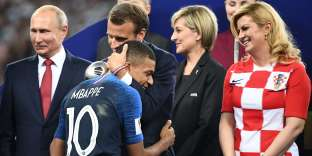 TOPSHOT - French President Emmanuel Macron (2L) congratulates France's forward Kylian Mbappe (3L) between Russian President Vladimir Putin (L) and Croatian President Kolinda Grabar-Kitarovic (R) during the trophy ceremony after the Russia 2018 World Cup final football match between France and Croatia at the Luzhniki Stadium in Moscow on July 15, 2018. RESTRICTED TO EDITORIAL USE - NO MOBILE PUSH ALERTS/DOWNLOADS / AFP / FRANCK FIFE / RESTRICTED TO EDITORIAL USE - NO MOBILE PUSH ALERTS/DOWNLOADS