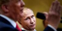 """Russia's President Vladimir Putin listens while US President Donald Trump speaks during a press conference at Finland's Presidential Palace July 16, 2018 in Helsinki, Finland. The US and Russian leaders opened an historic summit in Helsinki, with Donald Trump promising an """"extraordinary relationship"""" and Vladimir Putin saying it was high time to thrash out disputes around the world. / AFP / Brendan Smialowski"""