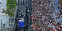 France's fans greet France's national football team players as they celebrate on the roof of a bus while they parade down the Champs-Elysee avenue in Paris, on July 16, 2018 after winning the Russia 2018 World Cup final football match. / AFP / Bertrand GUAY