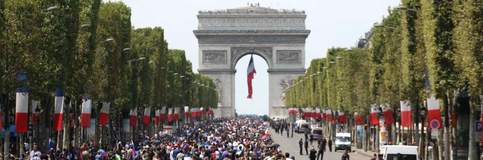 TOPSHOT - Supporters gather on the Champs-Elysees avenue near the Arch of Triumph (Arc de Triomphe) in Paris on July 16, 2018 as they wait for the arrival of the French national football team for celebrations after France won the Russia 2018 World Cup final football match on the eve. / AFP / ZAKARIA ABDELKAFI