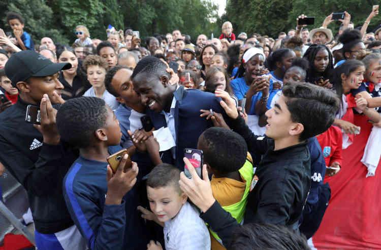 Bain de foule parmi les 1 500 invités. A l'Elysée, le défenseur français Benjamin Mendy est entouré par de jeunes joueurs qui ont été conviés à la récpetion de l'Elysée, à Paris, le 16 juillet.