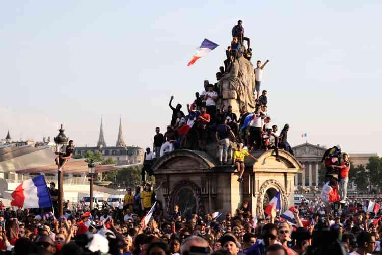 Des supporteurs attendent sur la place de la Concorde, devant l'hôtel de luxe le Crillon, la sortie de l'Elysée de l'équipe nationale française.