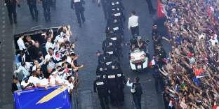 Un important cordon de sécurité séparait les joueurs de la foule, sur les Champs-Elysées, lundi 16 juillet.