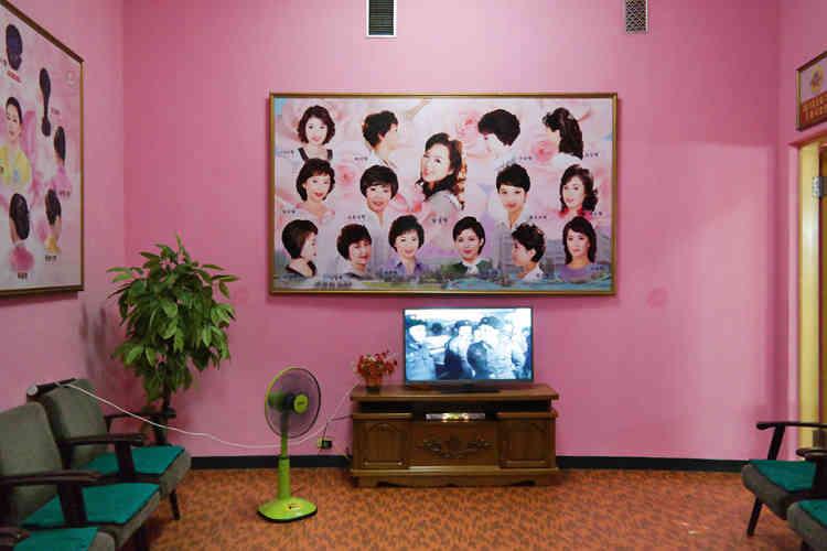 """«Une gamme de coupes de cheveux pour dames est exposée dans la salle d'attente du salon de coiffure au complexe de santé et de loisirs Changgwang. Construit le long de la rivière Pothong, c'était le centre de santé phare de la ville de Pyongyang lorsqu'il a ouvert, en 1980. Les clientes peuvent choisir parmi des coupes populaires, comme """"cascade""""ou """"nuage"""". D'une surface de presque 40000mètres carrés, ce complexe massif contient un sauna, des bains publics, un salon de beauté et des piscines.»"""