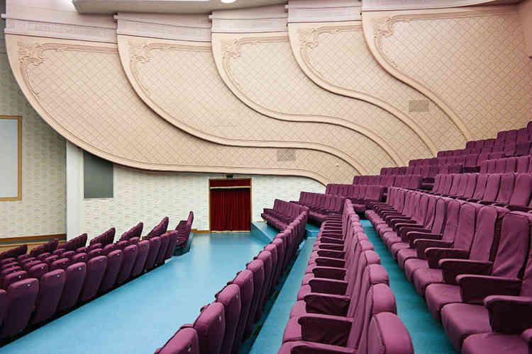 """«Le Grand Théâtre de Pyongyang abrite l'un des lieux les plus importants de la capitale pour des mises en scène et des opéras révolutionnaires. Construit en 1989, il est rénové en 2007, et a été habillé de verre miroir vert. Le théâtre a été décoré de murs insonorisants de couleur pêche, de fauteuils betterave rembourrés et d'un sol vinyle bleu clair. Jugés """"trop démodés"""", les parquets en bois ont été arrachés –un sort qui menace de plus en plus les intérieurs de style soviétique.»"""