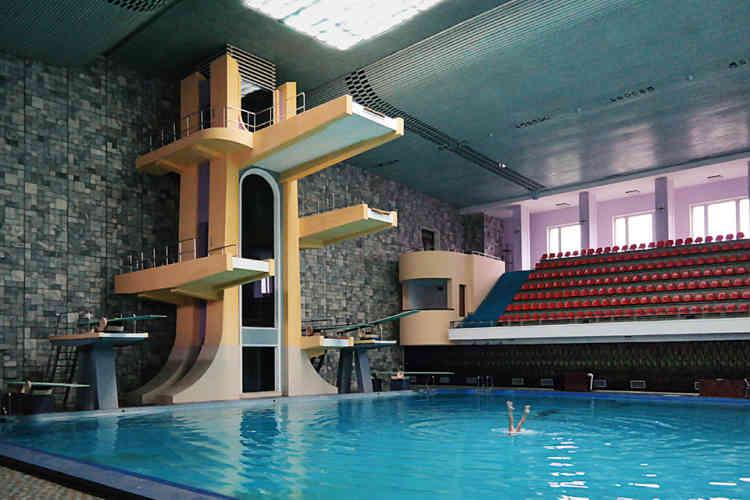 «La piscine principale du complexe de santé et de loisirs Changgwang est équipée d'une audacieuse tour de plongeoirs. Dans un esprit futuriste, on accède aux différents niveaux par un ascenseur mécanique dont la cage est en verre fumé. Le bâtiment comporte un reste de raffinement inhabituel pour un centre de loisirs public: les sols sont doublés de carreaux de mosaïques à motifs; les murs sont revêtus de marbre et les fenêtres intérieures sont remplies de blocs fleuris de verre coulé et coloré.»