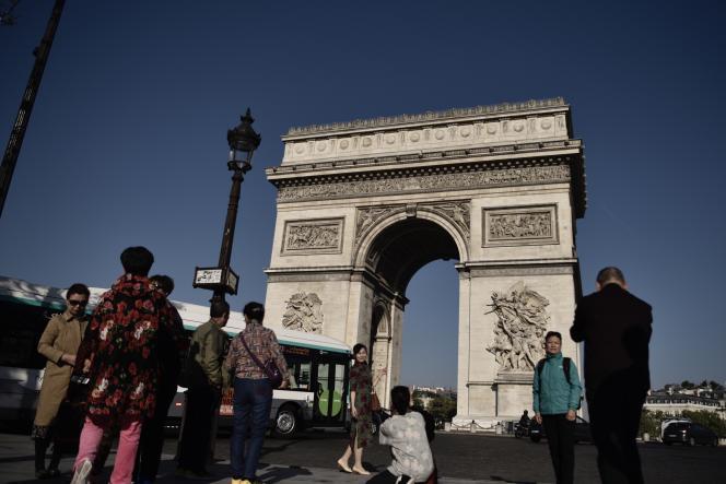 Des touristes devant l'Arc de triomphe sur les Champs-Elysées, à Paris, en avril 2017.