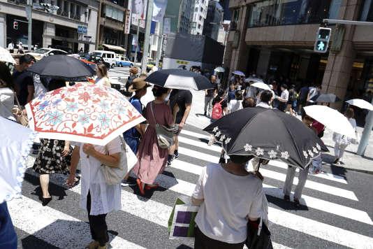 De nombreux passants se munissent d'ombrelles pour se protéger de la chaleur à Tokyo.