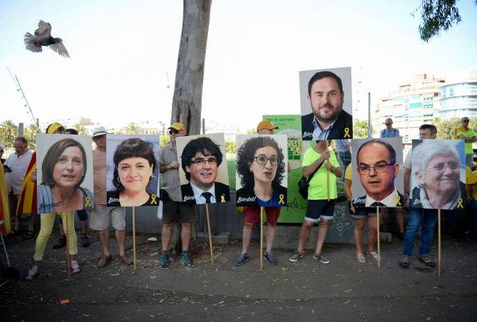 Des manifestants brandissent les portraits des dirigeants catalans concernés par desmandats d'arrêt internationaux, à Barcelone le 14 juillet.