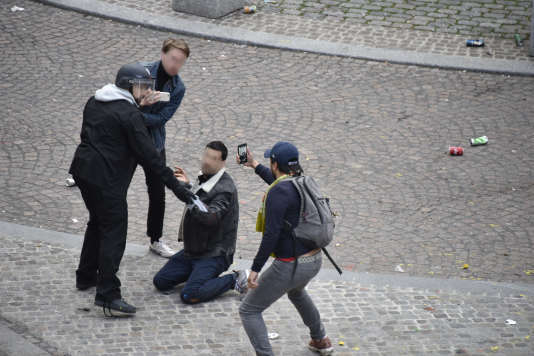 Alexandre Benalla maintient à terre le jeune manifestant, place de la Contrescarpe à Paris, tandis qu'un homme filme la scène, le 1er mai.