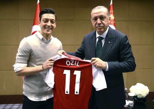 Mesut Ozil pose le 13 mai 2018 avec le président turc, Recep Tayipp Erdogan, et lui offre un maillot de son équipe, Arsenal.
