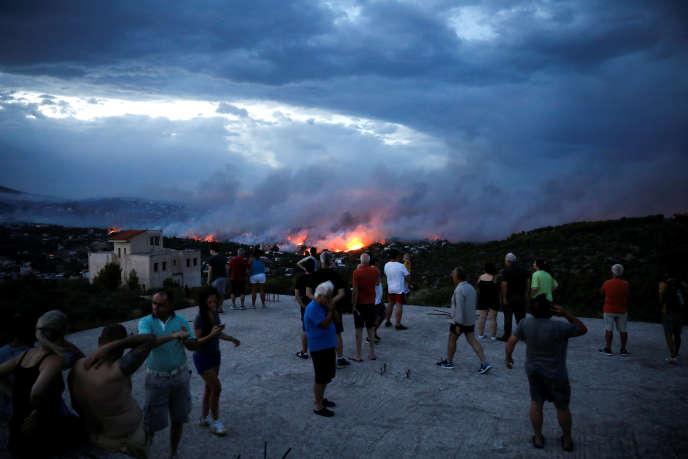 Des Grecs regardant les feux sur Rafina, près d'Athènes, lundi 23 juillet.