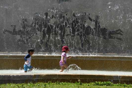 Des enfant jouent dans une fontaine d'un parc de Tokyo, alors que la ville connaît des température record, le 20 juillet.