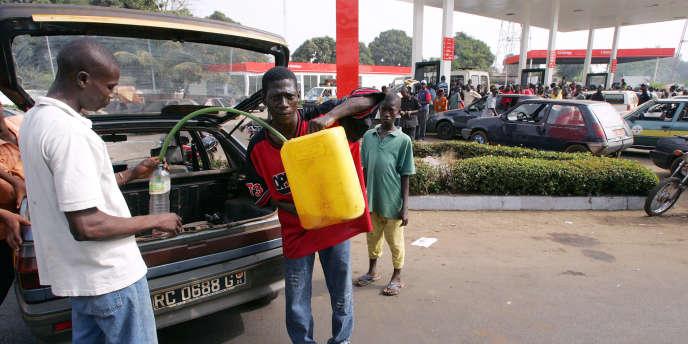Un homme vend du carburant au « marché noir» à côté d'une station service de Conakry, en janvier 2007.