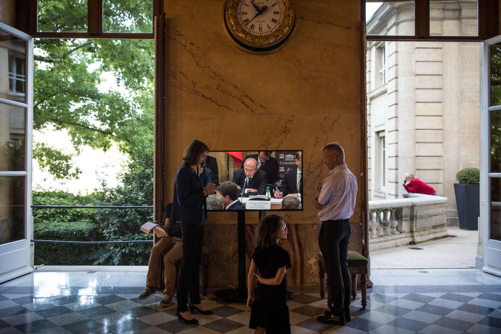 Dans le Palais-Bourbon, une seule voix s'élève, sortie des téléviseurs qui retransmettent tous la même réunion de commission. Les agents de l'Assemblée s'arrêtent pour regarder.