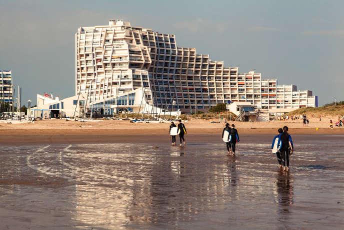 A Saint-Jean-de-Monts, des surfeurs marchent sur la plage devant l'immeuble Arc-en-ciel.