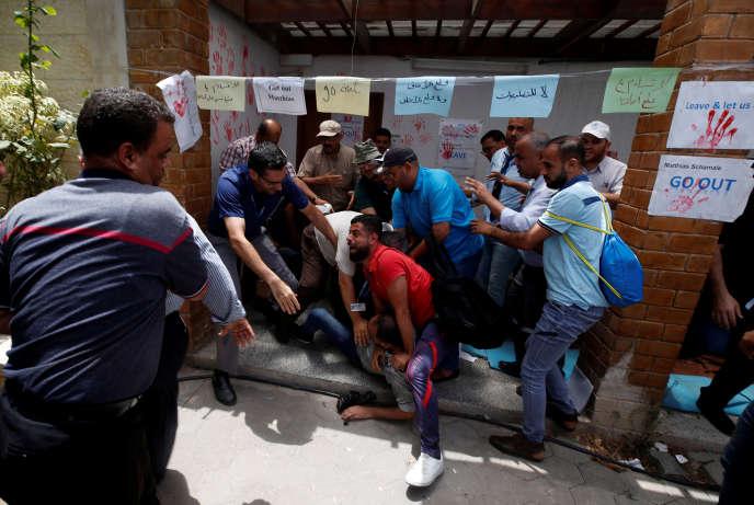 Des personnes tentent de dissuader un employé de l'UNRWA de s'immoler par le feu, le 25 juillet au siège de l'agence à Gaza.