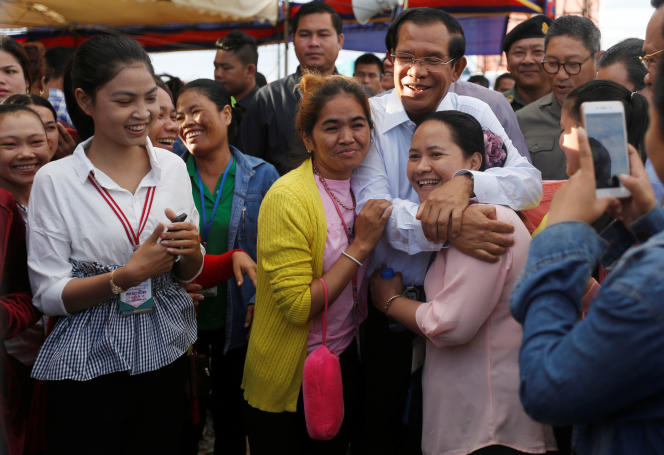 Le premier ministre cambodgien, Hun Sen, avec des employées du secteur textile, dans la province de Kandal, le 4 juillet.