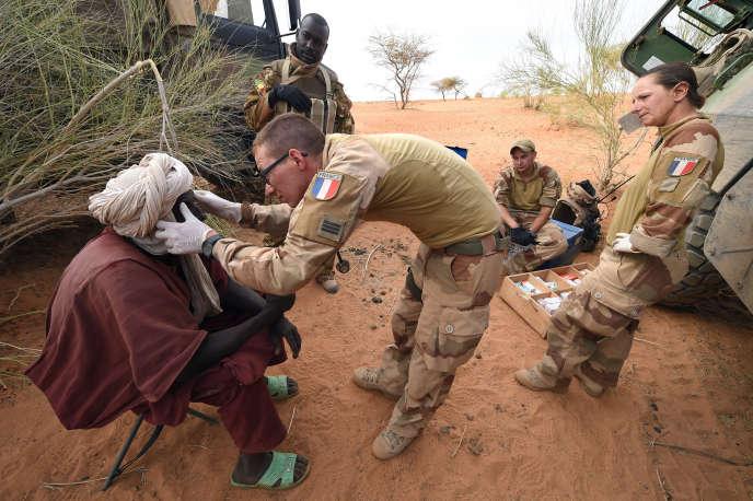 Un soldat français apporte de l'aide médicale à un citoyen malien dans la région de Tombouctou, en mars 2016.