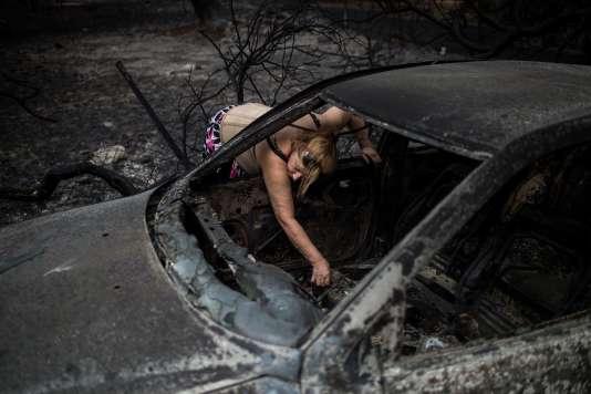 Une femme cherche ses papiers dans sa voiture brûlée, à Mati, près d'Athènes (Grèce), le 24 juillet.