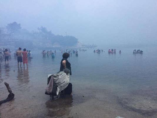 Les habitants se réfugient dans la mer alors que la fumée continue d'envahir le village de Mati, près d'Athènes, le 24 juillet.