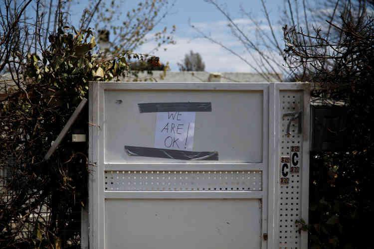 Un écriteau « nous allons bien» a été scotché sur une porte dans le village de Mati, le25juillet.