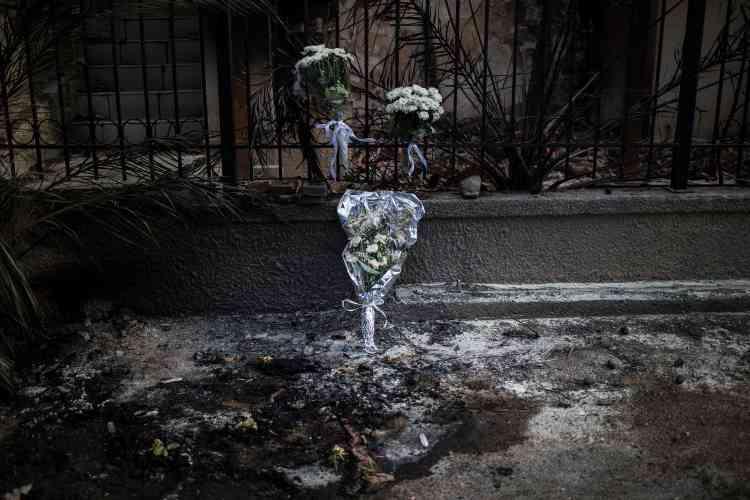 Devant une maison où deux personnes ont été retrouvées mortes, à Mati, le 26juillet. Mardi, le pays était sous le choc des découvertes macabres, enparticuliercelle de26personnes, dont des enfants, carbonisées.