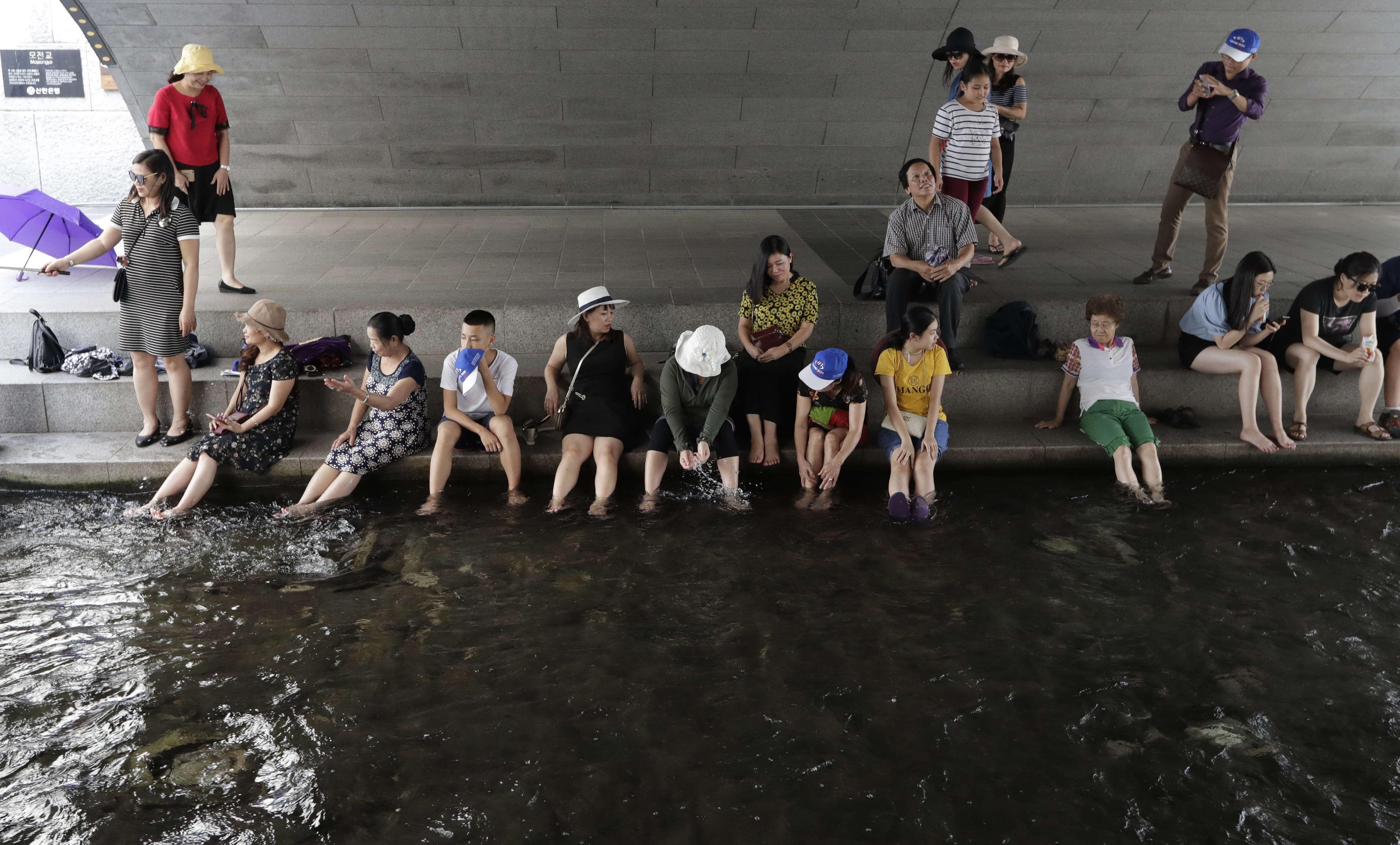 Des visiteurs se reposent à l'ombre dans le courant duCheonggyecheon, dans le centre-ville de Séoul, en Corée du Sud, le 23juillet. La vague de chaleur qui s'est emparée d'une large partie du Japon a également atteint la Corée du Sud voisine.