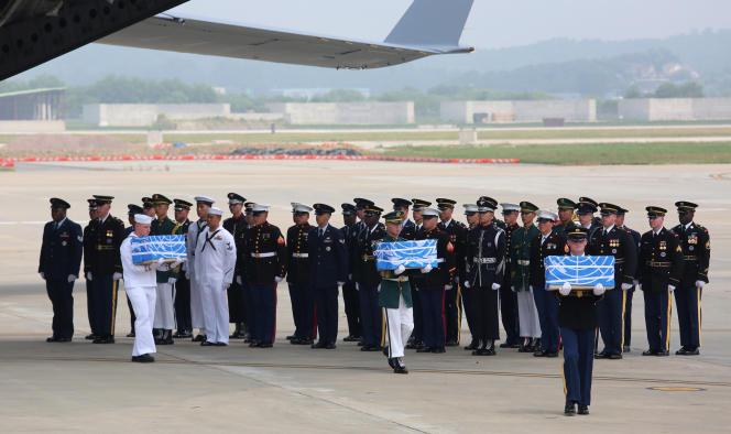 Des officiels transportant les boîtes qui contiennent des restes de soldats américains tués pendant la guerre de Corée, sur la base d'Osan en Corée du Sud, le 27 juillet.