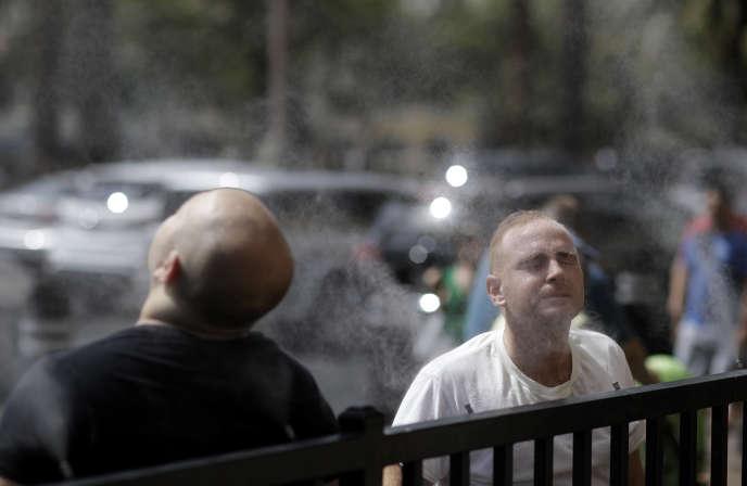 Des passants s'arrêtent pour profiter des brumisateurs, àLas Vegas (Nevada), le 24juillet.