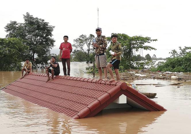 Des villageois réfugiés sur un toit, au lendemain de l'effondrement d'un barrage, le 24 juilet, dans le district d'Attapeu, au sud-est du Laos.