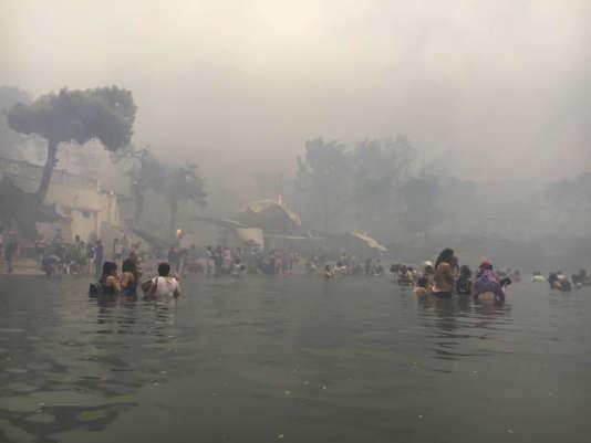 Des habitants tentent d'échapper aux flammes en restant dans la mer, à Mati, le 23 juillet.