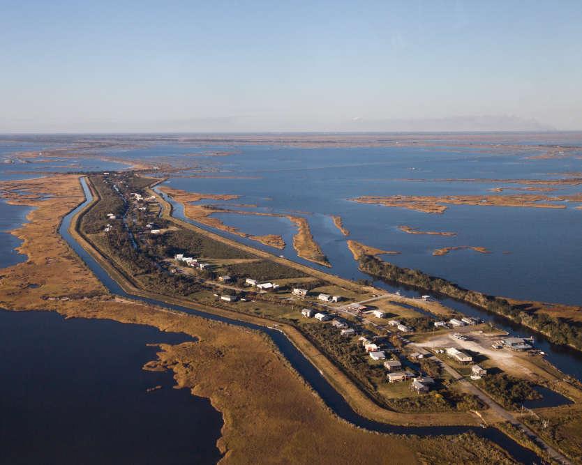 L'Isle de Jean Charles n'est plus qu'un mince bandeau de terre de 8 km de long. L'île a perdu 98 % de sa surface depuis 1955 du fait de l'érosion côtière et de l'exploitation pétrolière.