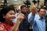 Le premier ministre cambodgien, Hun Sen (à droite), et son épouse, Bun Rany, montrent leur index taché d'encre, marque de leur passage aux urnes, à Takhmao, le 29 juillet.