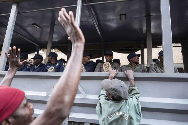 Un camion des forces de l'ordre passe devant despartisans du MDCmanifestant leur joie, à Harare (Zimbabwe), le 31juillet2018. Le parti d'opposition dit avoir remporté l'élection présidentielle.