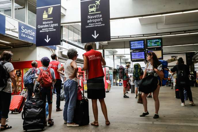 Un agent SNCF conseille des usagers à la gare Montparnasse, lundi 30 juillet.