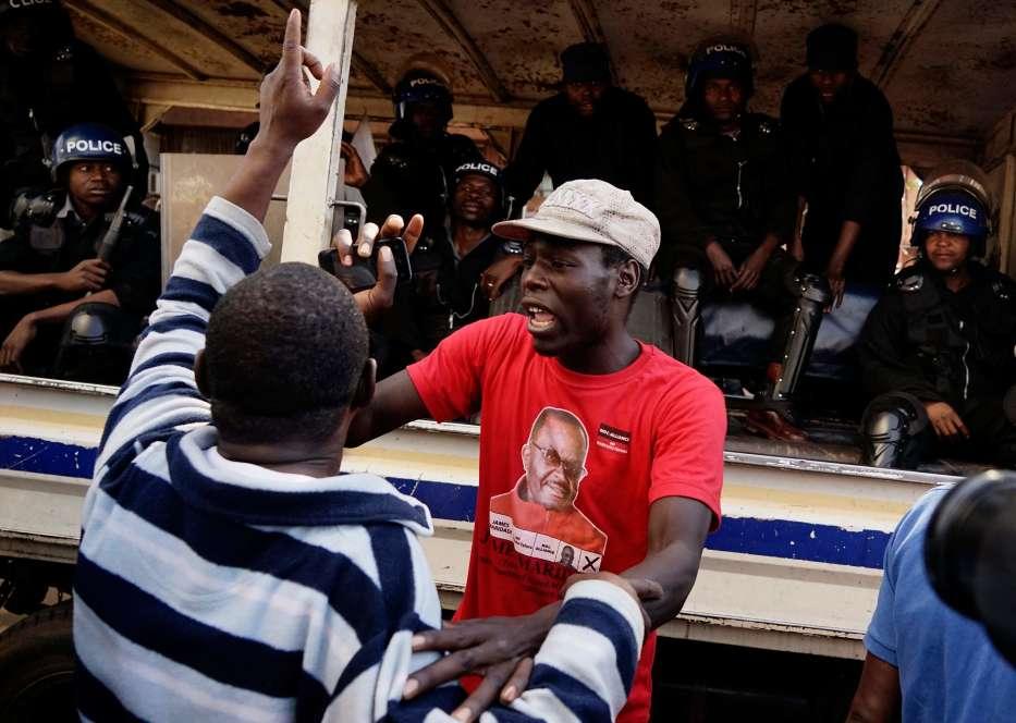 Des partisans du parti d'opposition MDC Alliance devant des policiers venus assurer la sécurité du siège de la Commission électorale du Zimbabwe (ZEC).Selon les résultats publiés mercredi1eraoût par la commission électorale, la ZANU-PF a remporté plus de deux tiers des sièges de l'Assemblée nationale.