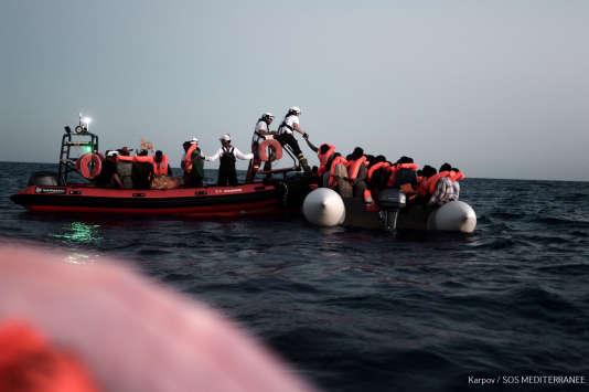 Des membres de l'ONG SOS Méditerranée portent secours à des migrants avant de les faire embarquer sur l'Aquarius, le 9 juin.