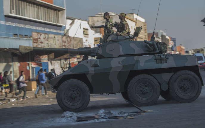 Un blindé fait fuir les partisans de l'opposition, à Harare (Zimbabwe), le 1er août.