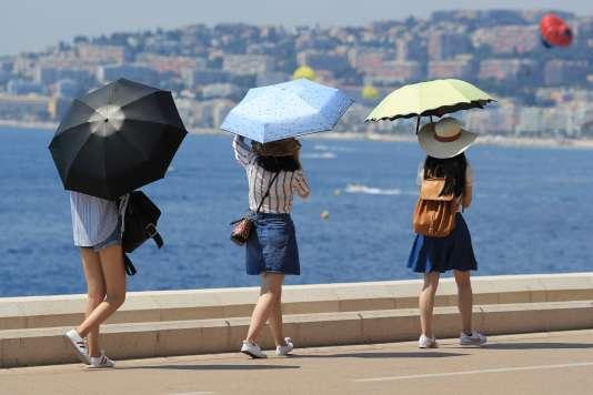 Des touristes s'abritent sous des parapluies, à Nice.