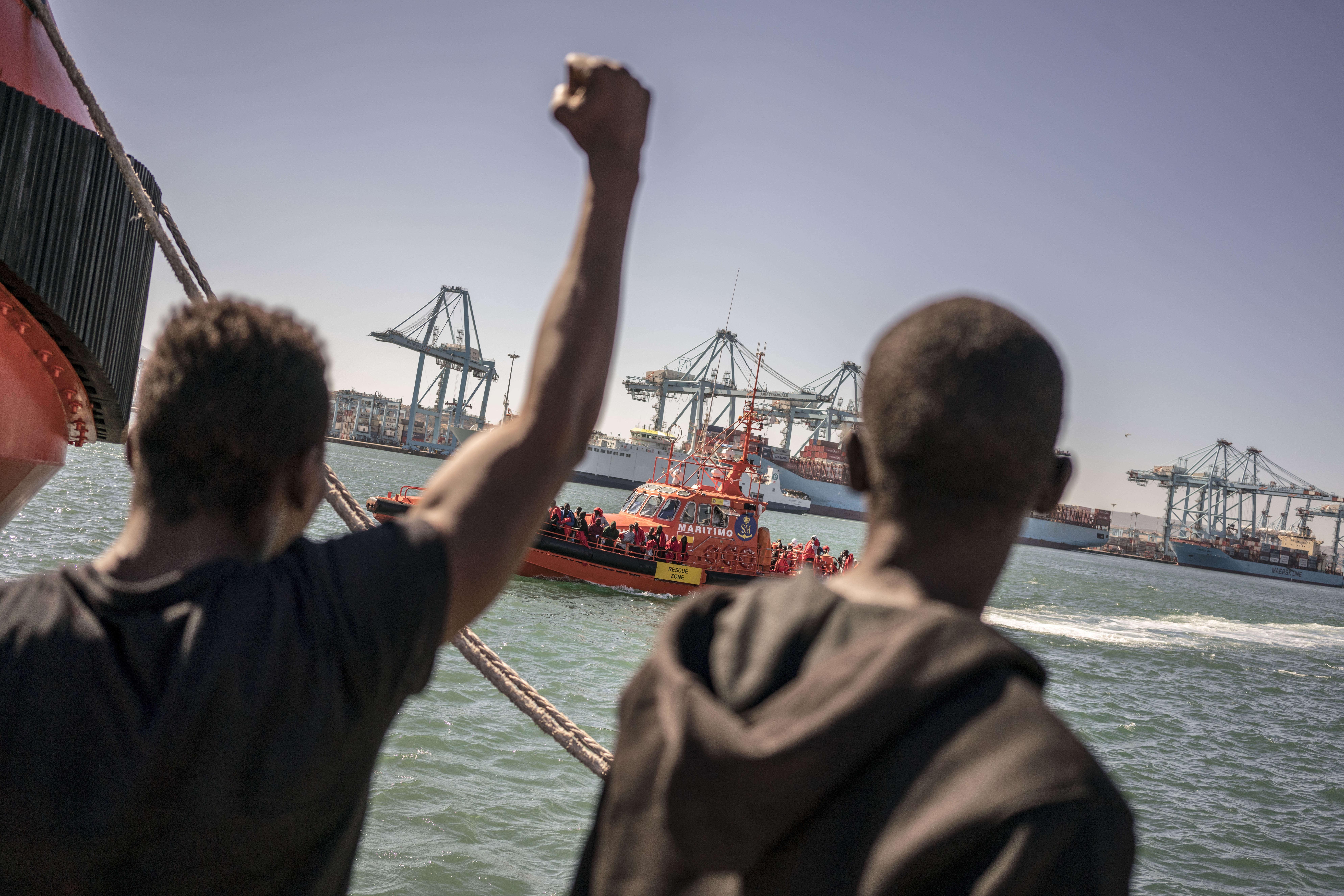 Des migrants font signe à un nouveau bateau de sauvetage tout juste arrivé au port d'Algésiras.