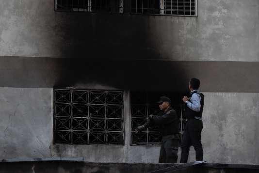 Les forces de sécurité inspectent un immeuble sur laquelle on voit des traces d'explosion, le 4 août à Caracas.