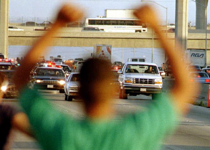 O.J. Simpson (dans la Ford Bronco, à droite) poursuivi par la police, à Los Angeles, le 17 juin 1994, et salué par un sympathisant.