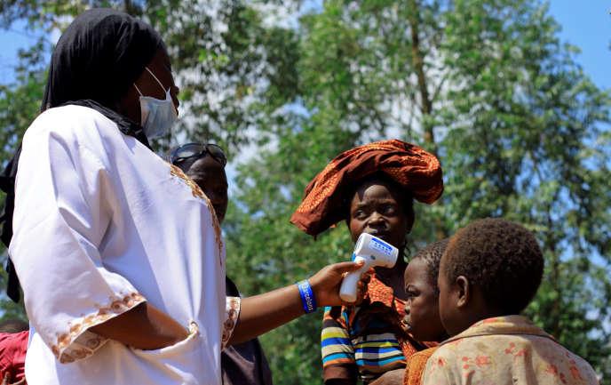 Une aide-soignante prend la température d'un enfant avant une campagne de vaccination contre le virus Ebola, le 8 août, près de Mangina.