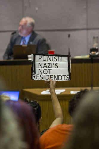 Une femme brandit un panneau«Punissez les nazis, pas les habitants» pendant un conseil municipal, à propos de l'anniversaire des émeutes.L'Etat d'urgence a été proclamé par le gouverneur de Virginie, et la police va fermer l'accès des véhicules dans le centre-ville.