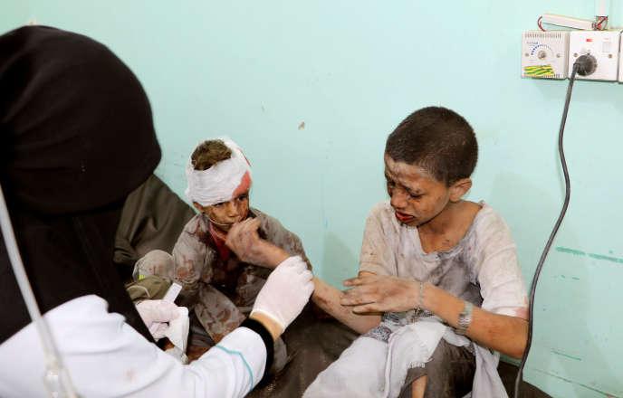 Un médecin soigne des enfants blessés à cause d'un raid aérien contre un bus à Saada, au Yémen, le 9 août.